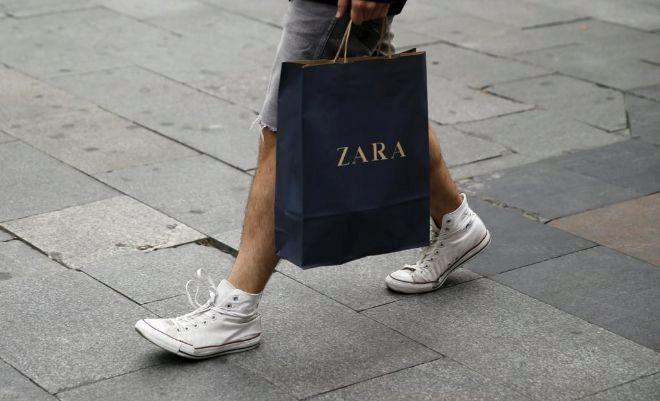 Un hombre pasea con una bolsa de Zara por Madrid