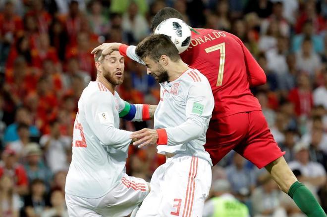Sergio Ramos y Piqué saltan con Cristiano en una acción del primer partido.