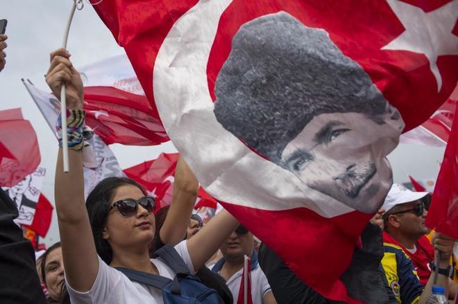 Una simpatizante del candidato turco Muharren Ince, junto a una bandera de Ataturk, en Estambul.