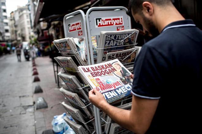 """Un hombre lee un periódico con el titular """"primer presidente Erdogan""""."""
