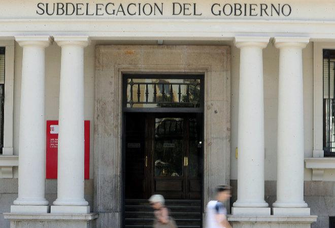 Dos personas caminan frente a la Subdelegación del Gobierno de Castellón.