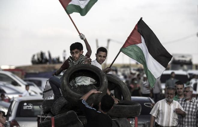 Jóvenes manifestantes palestinos con banderas y neumáticos en Gaza.