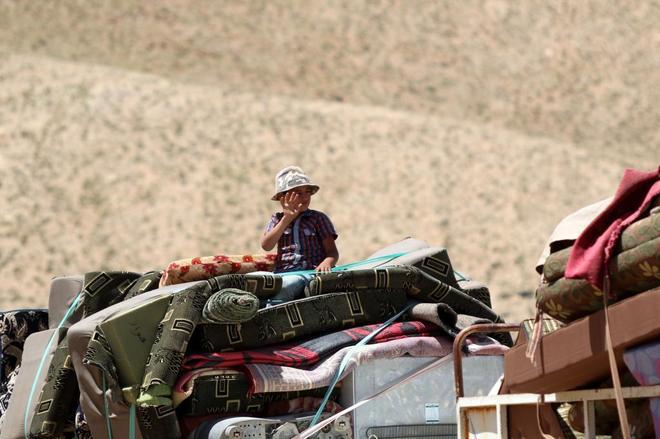 Un niño sirio saluda mientras cruza la frontera entre Siria y...