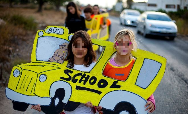 Dos niñas en una protesta por los recortes en la línea del autobús escolar.