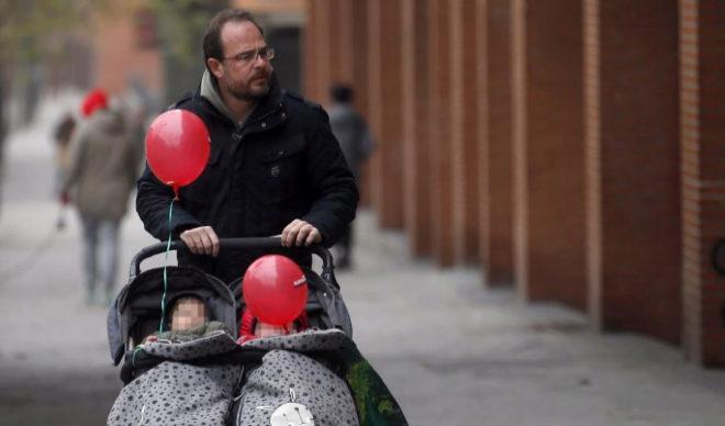 Un padre empuja el carrito de sus bebés.