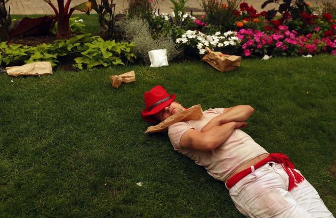 Un turista duerme en un parque antes del inicio del encierro de esta...