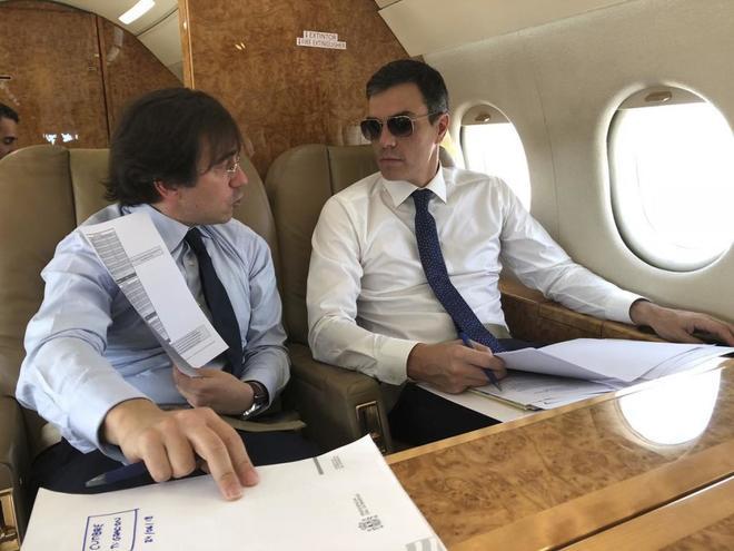 El presidente Pedro Sánchez conversa con su asesor internacional José Manuel Albares en el avión presidencial.