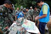 Los equipos de salvamento examinan un mapa antes de proceder al...