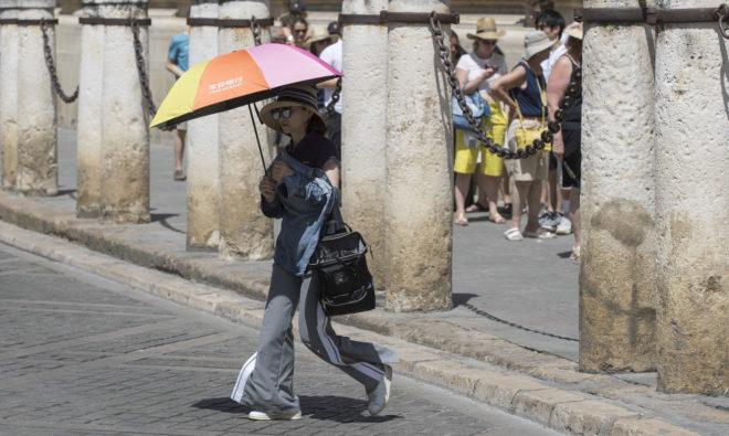 Una mujer se protege del sol con un paraguas junto a la Catedral de Sevilla.
