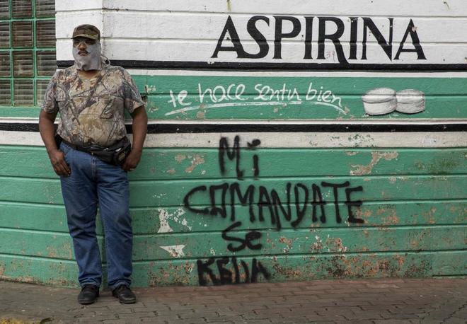 """Un hombre con la cara tapada junto a una pared en la que se lee """"Mi comandante se queda""""."""