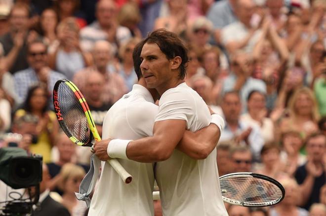 Nadal y Djokovic se abrazan después del partido en la Central de Wimbledon.