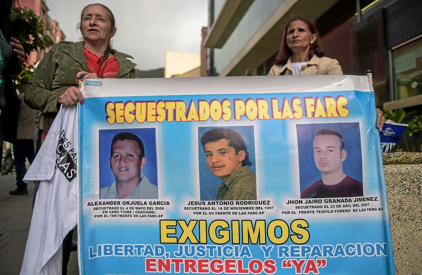 Dos mujeres portan un cartel con los rostros de tres secuestrados por las FARC, a las afueras del Tribunal Especial para la Paz, en Bogotá.