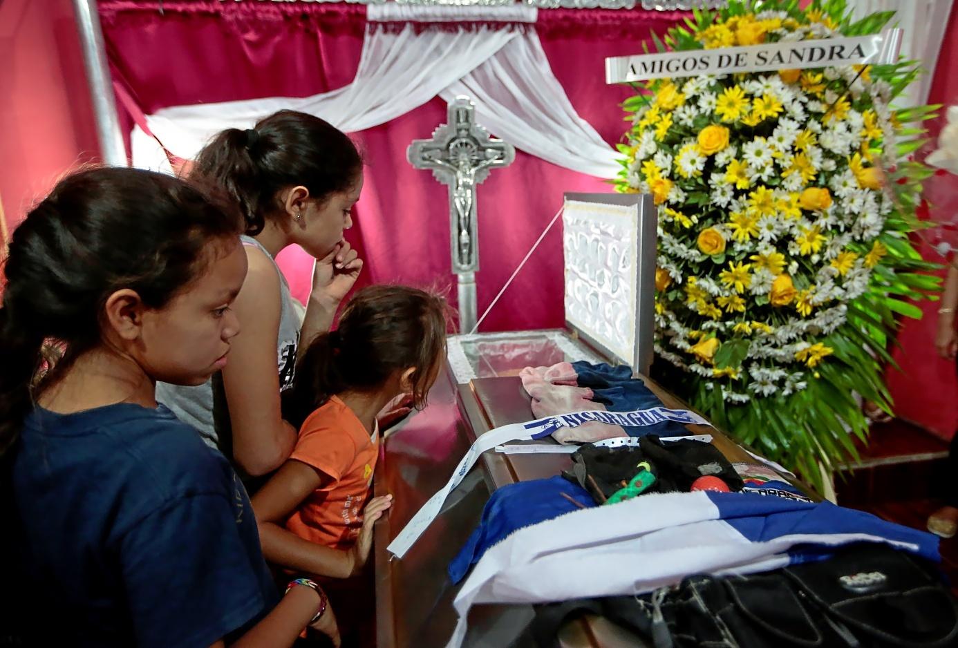 Tres niñas miran el interior de un ataud con el cuerpo de Gerald Jose Vasquez, muerto en las protestas universitarias contra Ortega en Managua