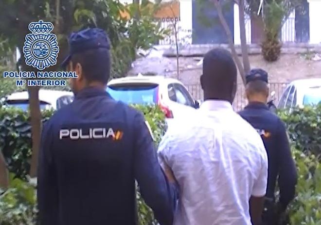 Agentes de la Policía escoltan a uno de los detenidos.