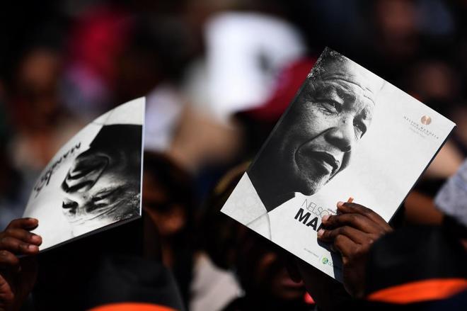 Varios asistentes se protegen del sol durante la conferencia 'Nelson Mandela' que rinde tributo a la figura del fallecido presidente sudafricano.