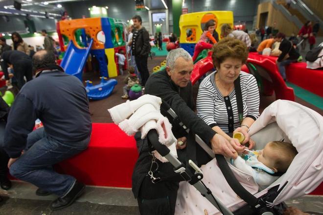 Varias generaciones reunidas en un parque infantil navideño en...