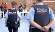 Dos 'mossos' observan una de las mesas constituidas para el...