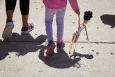 Una niña de cuatro años camina de la mano de su madre al salir del...