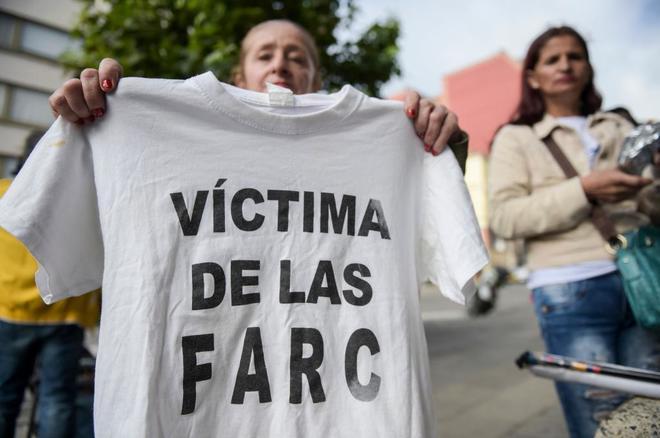 """Una mujer muestra una camiseta con la frase """"Víctima de las FARC""""."""