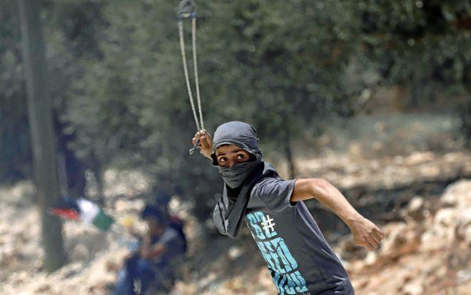 Un palestino lanza piedras hacia las tropas israelíes durante una protesta, en Kofr Qadom.