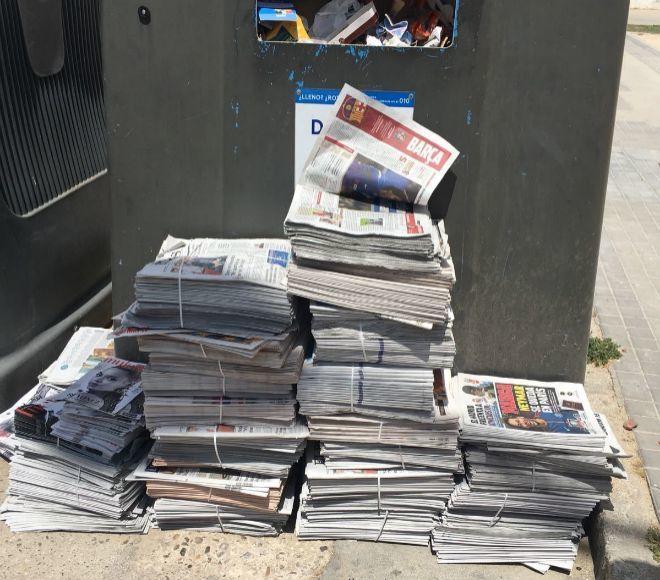Varios paquetes de periódicos, tirados anteayer junto a un contenedor de papel.
