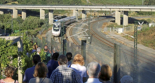 Varios ciudadanos observan el paso de un tren Alvia donde se produjo el accidente en 2013