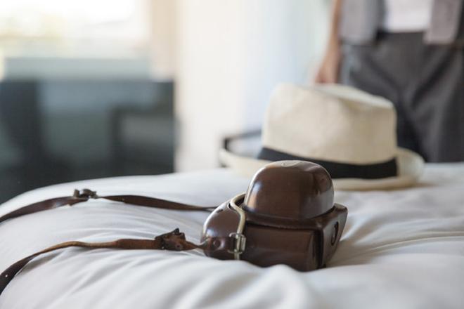 Un sombrero panamá y una cámara de fotos sobre la cama de un hotel.