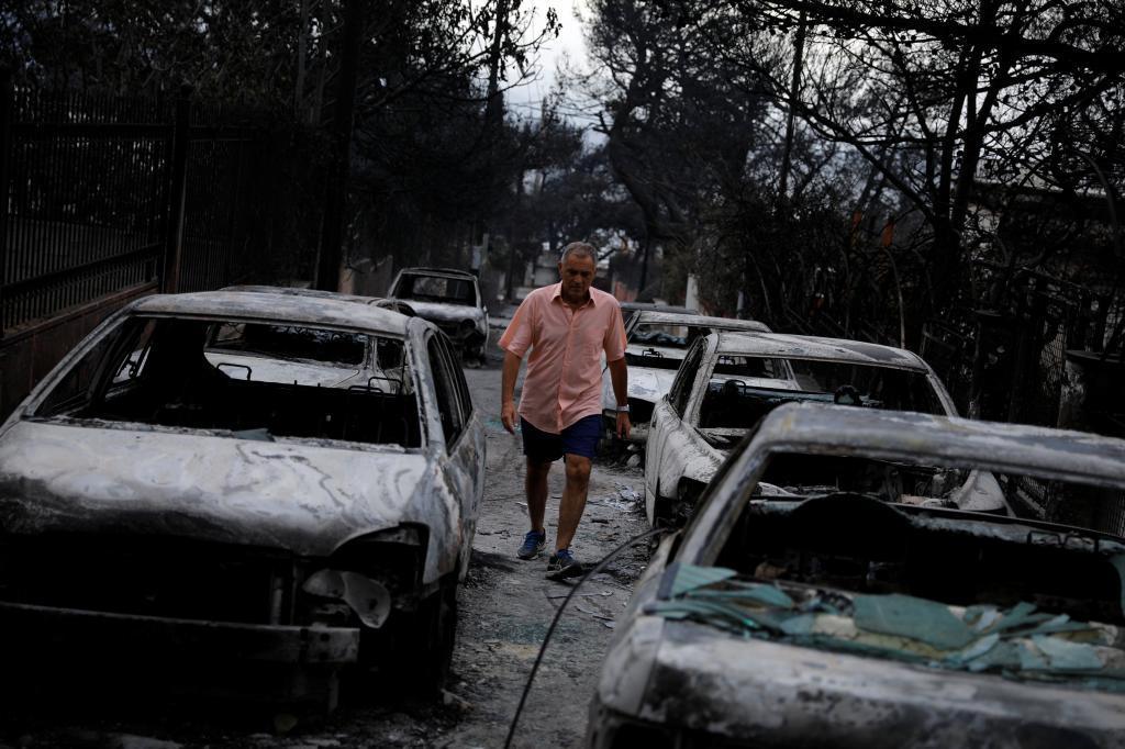 Un hombre camina entre varios coches calcinados.