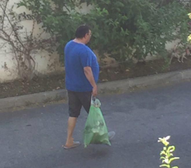 El okupa Juan Carlos C.B. saliendo del piso que tiene okupado a tirar la basura