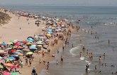 Miles de bañistas disfrutan del mar en la playa de Cullera, en...
