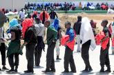 Un grupo de inmigrantes hace cola para recibir agua y comida