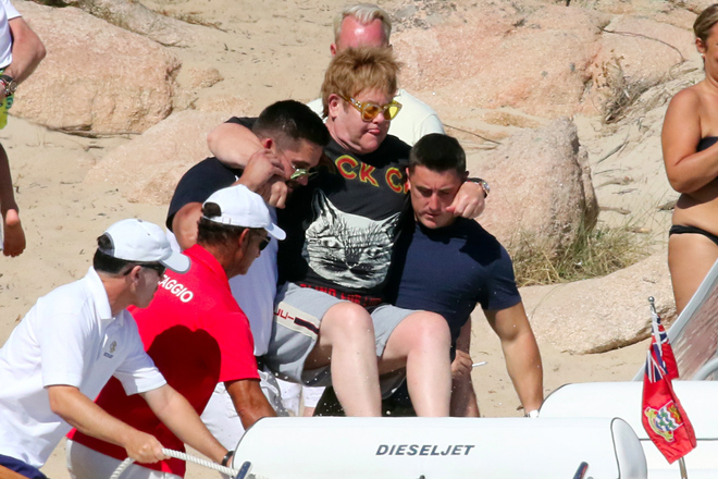 Elton John, en brazos de sus guardaespaldas en Porto Cervo, en...