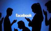 Varias personas consultan sus teléfonos junto al logo de Facebook