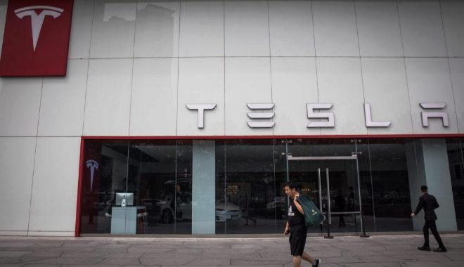 Dos hombres pasean por de la sede compañía estadounidense Tesla, en Pekín, China,