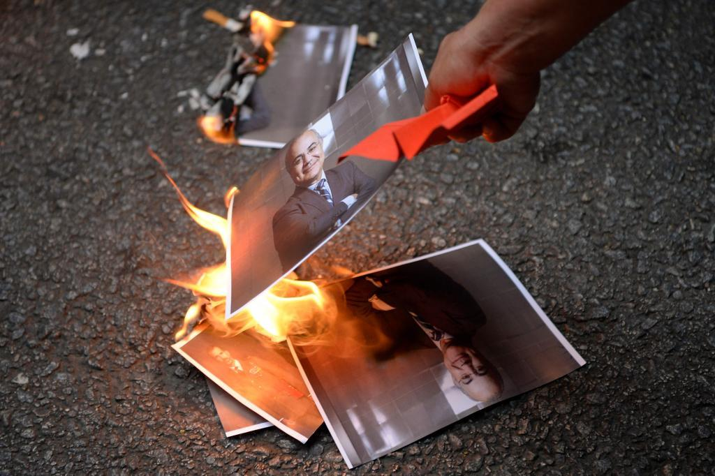 A protester sets fire to a photographs depicting Spanish Supreme Court judge Pablo Llarena, who ordered sending Catalan separatists to jail, during a demonstration called by local Republic Defence Committees (CDR) in Barcelona on August 2, 2018. / AFP PHOTO / Josep LAGO