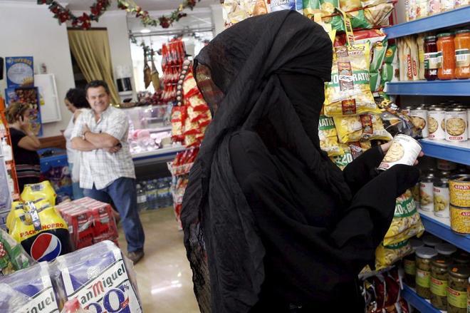 Una mujer con velo integral en un supermercado.
