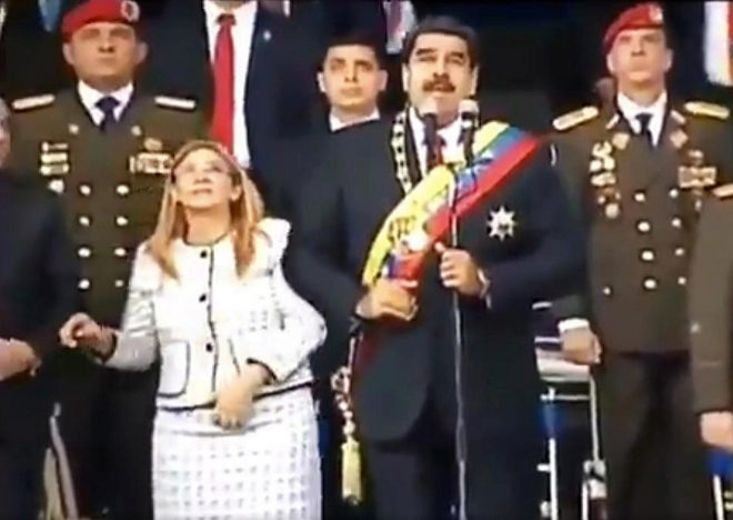 "Screengrab taken from a handout video released by Venezuelan Television (VTV) showing Venezuelan President Nicolas Maduro (C), his wife Cilia Flores (L) and military authorities reacting to a loud band during a ceremony to celebrate the 81st anniversary of the National Guard in Caracas on August 4, 2018. Maduro was unharmed after an exploding drone ""attack"", the minister of communication Jorge Rodriguez said following the incident, which saw uniformed military members break ranks and scatter after a loud bang interrupted the leader's remarks and caused him to look to the sky, according to images broadcast on state television. / AFP PHOTO / VENEZUELAN TELEVISION (VTV) / HO / RESTRICTED TO EDITORIAL USE - MANDATORY CREDIT ""AFP PHOTO / VENEZUELAN TELEVISION - VTV"" - NO MARKETING NO ADVERTISING CAMPAIGNS - DISTRIBUTED AS A SERVICE TO CLIENTS"