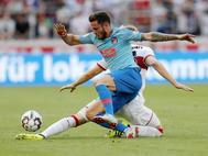 Saúl disputa un balón con un jugador del Stuttgart.