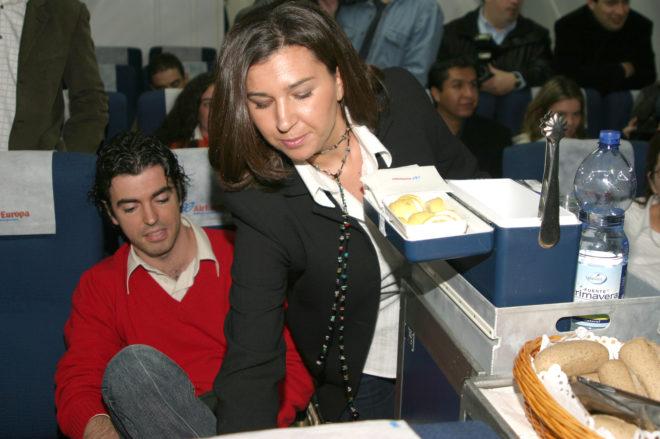 Una azafata sirve comida a un pasajero en un avión.