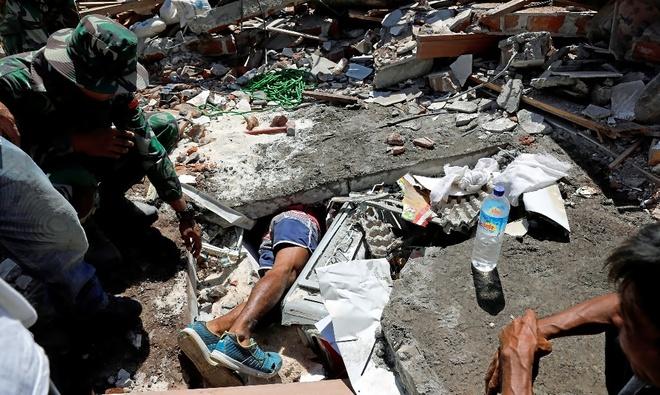 Un voluntario busca supervivientes bajo los escombros ante la mirada de los soldados, en Pemenang.