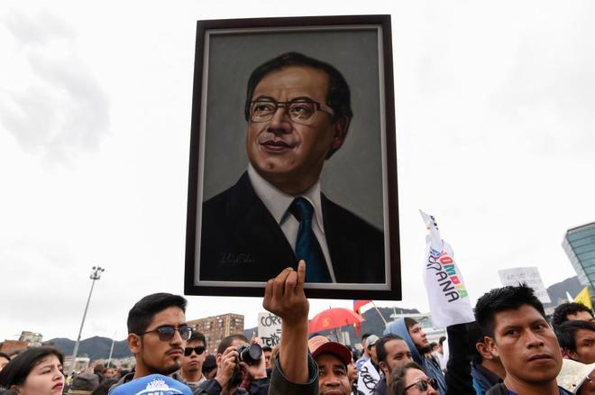 Un hombre sostiene la foto del ex candidato Petro en una manifestación.