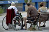 Un anciano en silla de ruedas junto a una residencia en Madrid con dos...