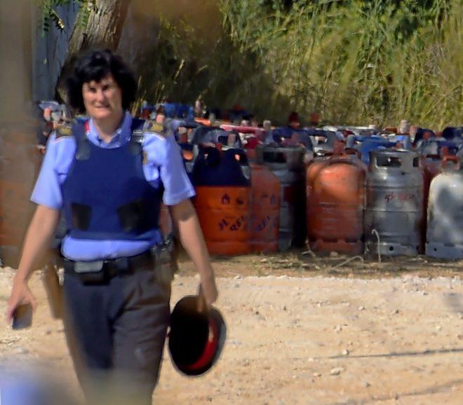 Una agente de los Mossos camina junto a unas bombonas de gas en la...