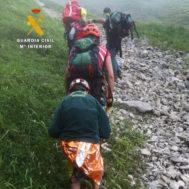 Miembros de la Guardia Civil trasladan al niño y a la mujer tras ser rescatados en los Picos de Europa.