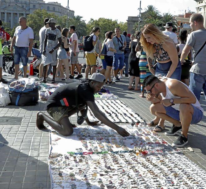 Un grupo de manteros despliega sus productos en el Paseo Colón de Barcelona