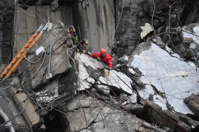 Los equipos de emergencias trabajan entre los escombros del puente derrumbado en Génova.