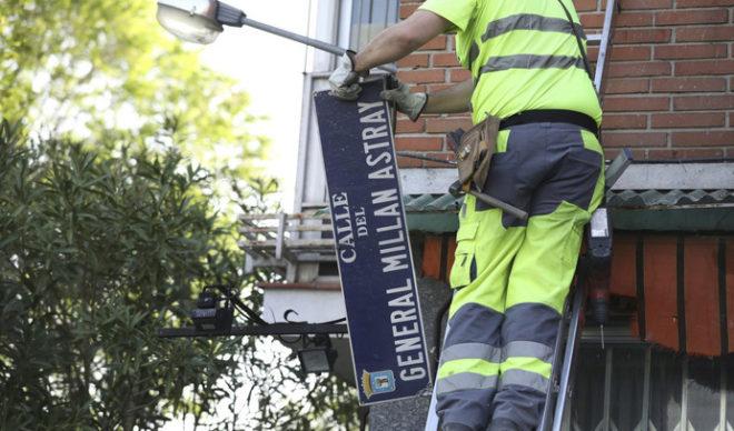 Un operario cambiando el nombre de la calle Millán Astray.