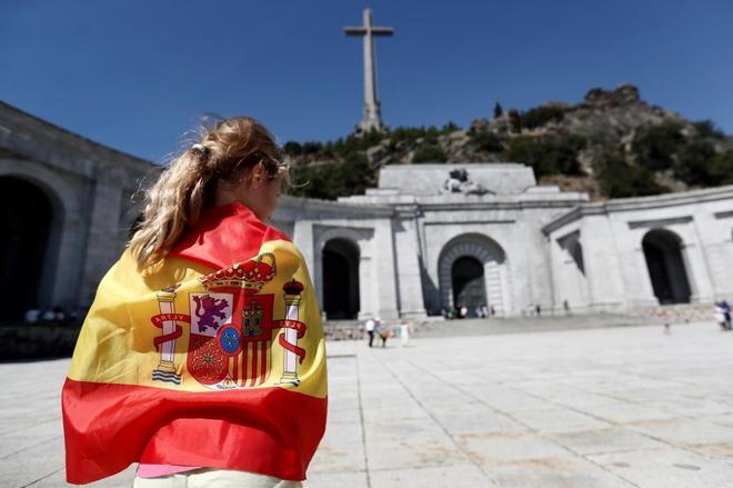 Una chica envuelta en la bandera de España entra en el Valle de los...