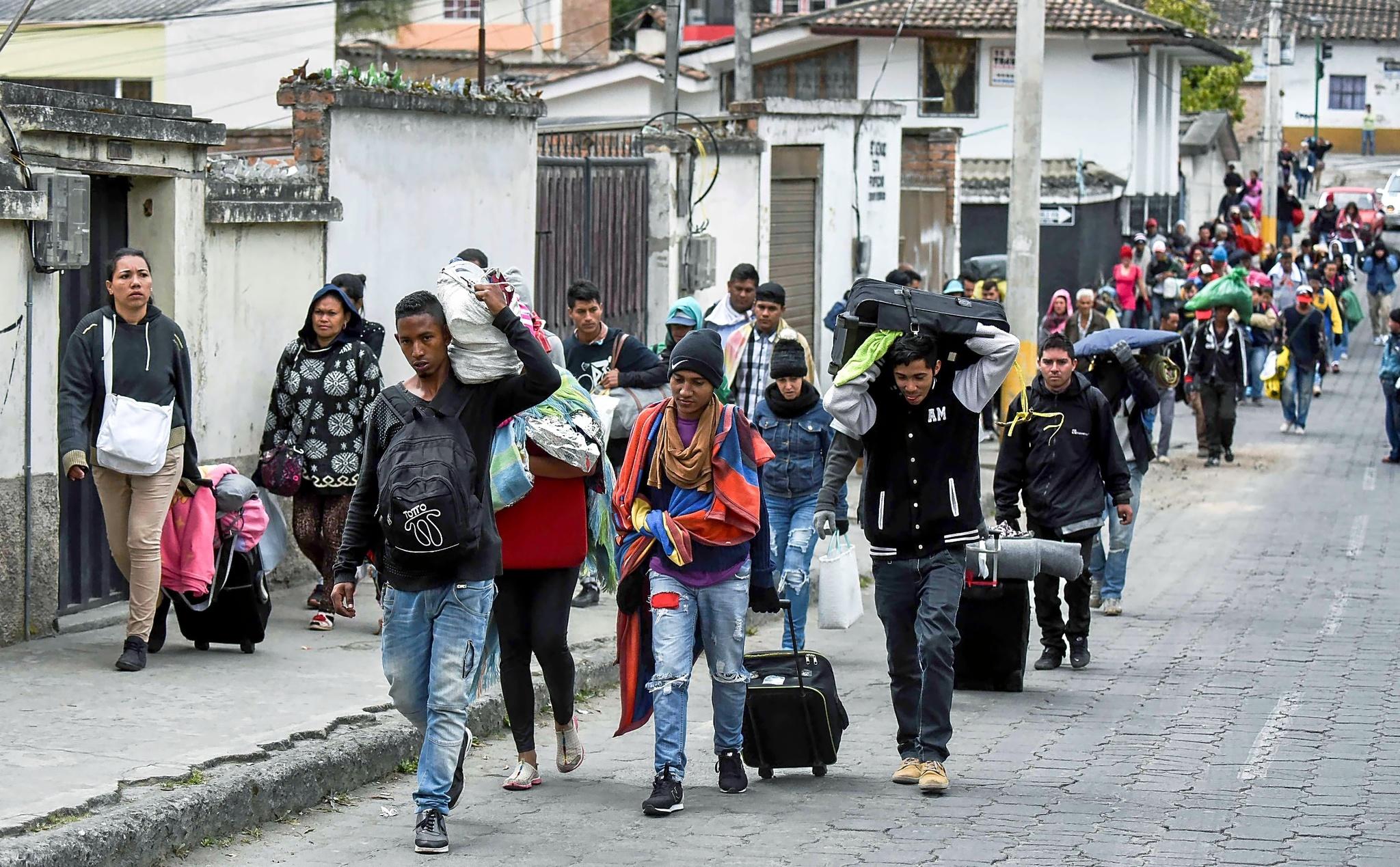 Migrantes venezolanos marchan hacia Perú por las calles de Tulcan,...