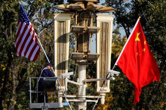 Un trabajador coloca una bandera estadounidense y una china para la...